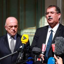 """Frankrikes inrikesminister Bernard Cazeneuve tillsammans med ordförande för Frankrikes muslimska råd Anouar Kbibech. Till höger en lapp som lyder """"sörjande moské"""", på moskén i Saint-Etienne-du-Rouvray."""
