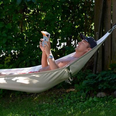 En man ligger i en hängmatta och använder en läsplatta.