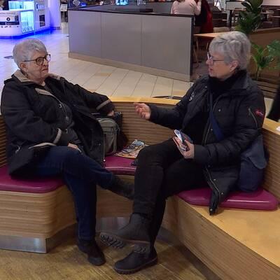 Lena och Rose-Marie Asplind sitter på en bänk i ett köpcentrum.