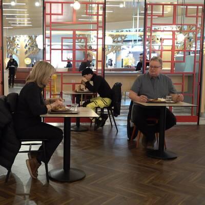 Besökare sitter utspridda och ensamma vid bord på servering