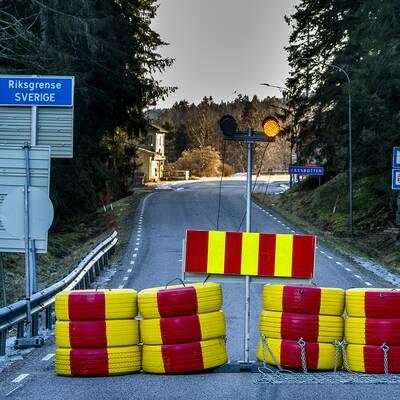 Rödoch gulmålade däck vid en väg där en vägskylt markerar gränsen mellan Sverige och Norge.