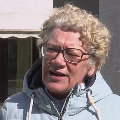 Korthårig kvinna med glasögon och ljusblå jacka framför ett vitt hus med vita markiser, samt blond kvinna i solstol framför vattnet.