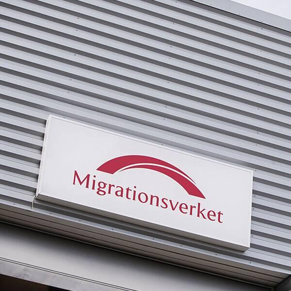 En fasadbild på en av migrationsverkets lokaler och en ung man med ryggen mot kameran.