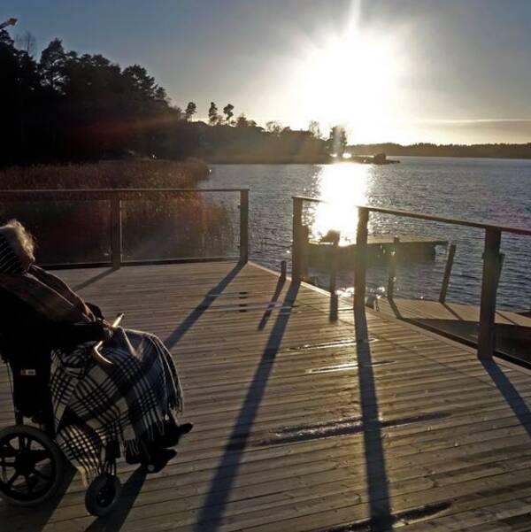 Äldre kvinna i rullstol njuter av höstsolen.