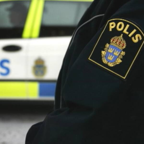 Polisemblem på armen till en polis, polisbil i bakgrunden