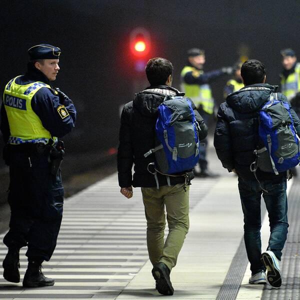 Polis eskorterar asylsökande från ett Öresundståg som stannat vid Hyllie station utanför Malmö efter genomförd gränskontroll.