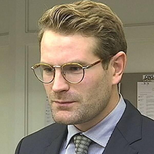 bild på Tobias Kaibring, korthårig med glasögon. Iklädd kavaj, blå skjorta och slips.