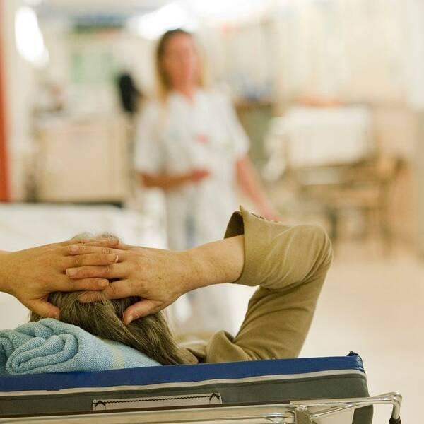 Kvinna på brits i sjukhuskorridor.