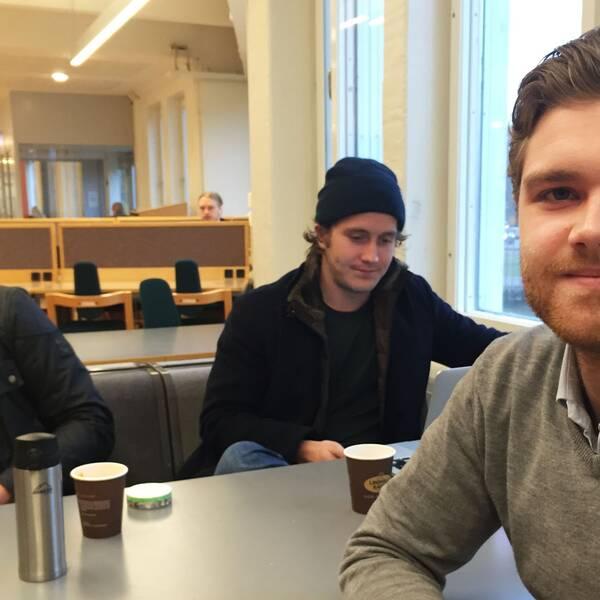 Tre studenter sitter vid ett bord. En ung man tittar in i kameran, han är till höger i bild.