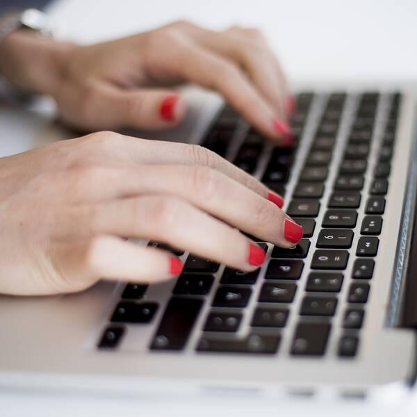 människa som skriver på dator