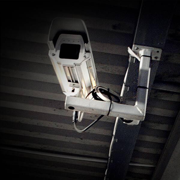 Övervakningskamera till vänster i bilden och på andra sidan kvällbild från Rinkebytorg med polisbil parkerad i förgrunden.