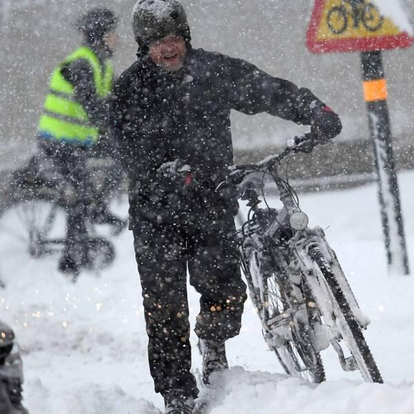 Cyklist leder cykel i snöoväder