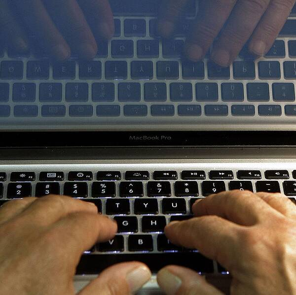 Ett par händer på ett tangentbord på en laptop.