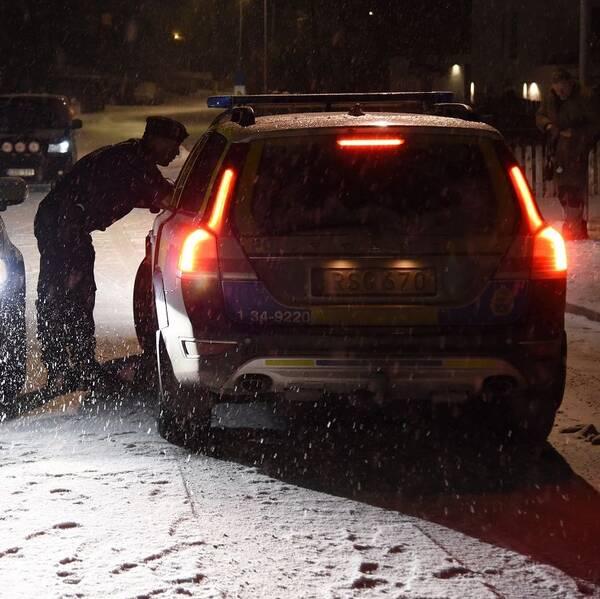 Två polisbilar och en polisman som böjer sig fram mot en bildörr