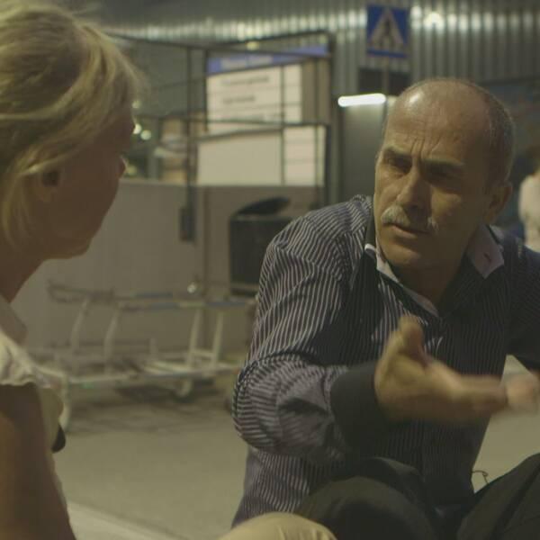 Kvinna i gul tröja intervjuar man i blårandig skjorta