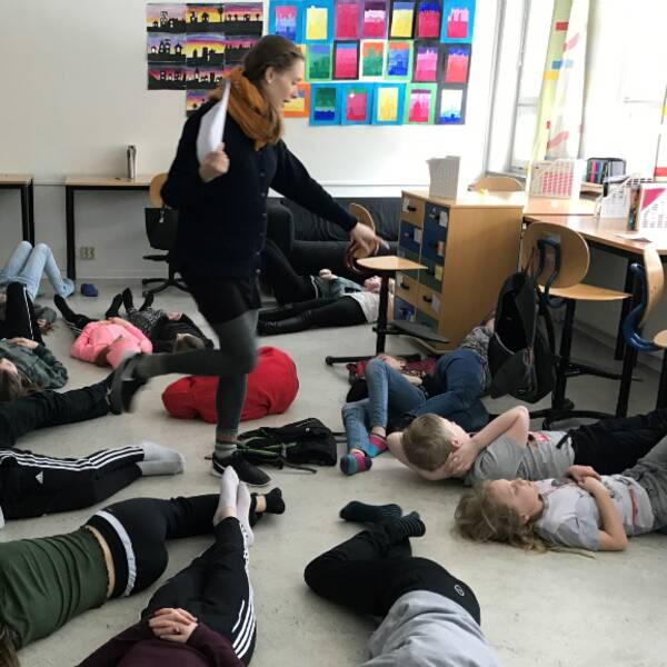 Elever ligger ner på klassrumsgolvet. Läraren instruerar.