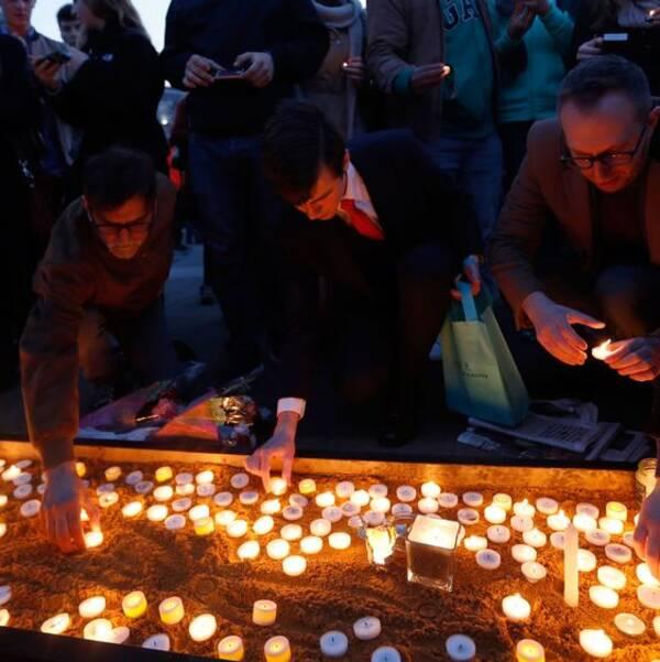Människor hedrar offren i attacken, tänder ljus