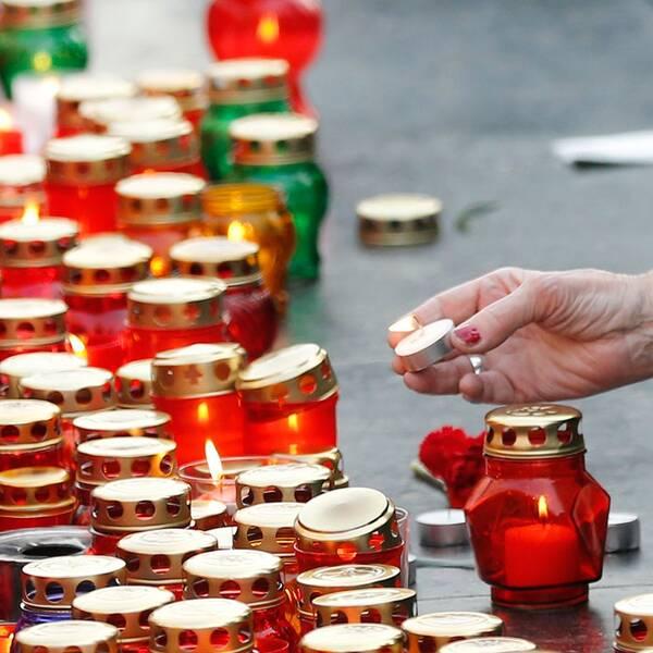 Sörjande lämnar ljus vid en minnesplats för offren i S:t Petersburg.