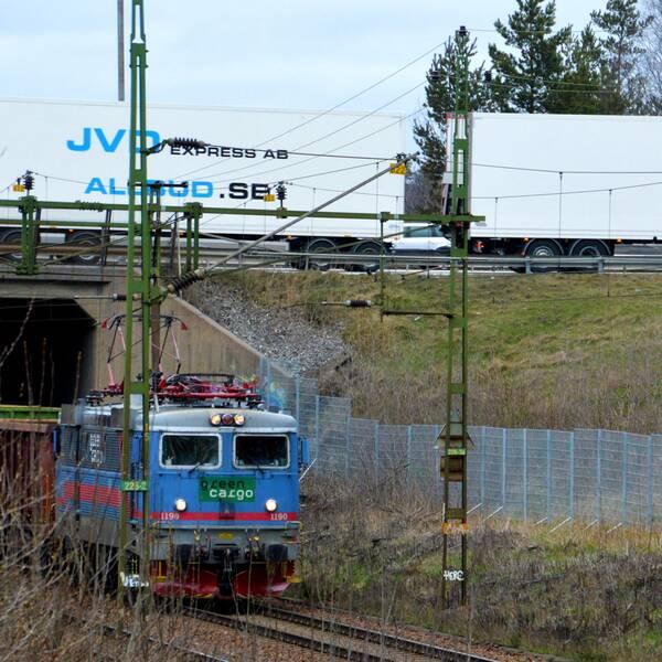 Ett tåg passerar i en tunnel under en väg. Ovanför färdas en lastbil.