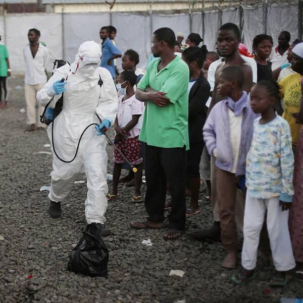 Personer som skrivits ut från en klinik i Liberia sprejas på väg ut därifrån.