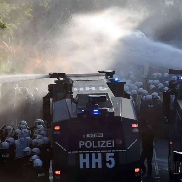 Polisen sprutar vatten på demonstranterna.