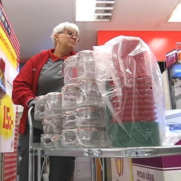 medelålders kvinna puttar vagn med varor i matbutik