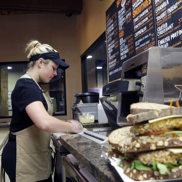 Ung kvinna som jobbar på kafé.