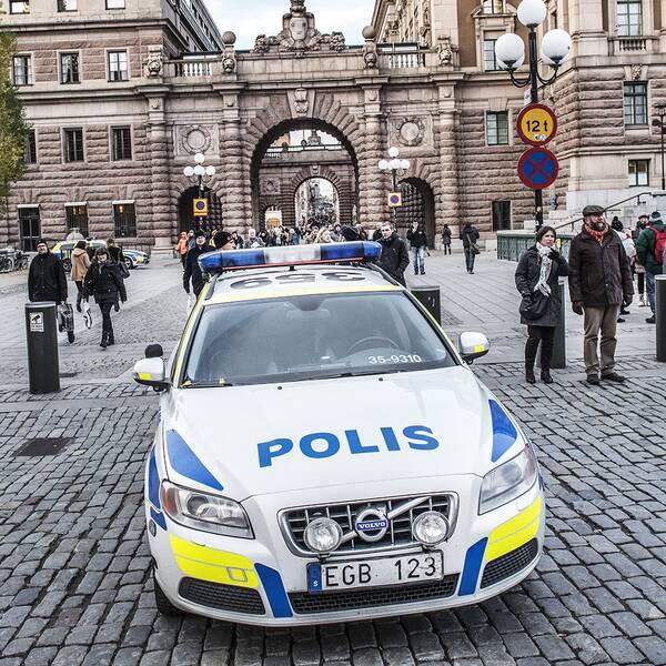 En polisbil framför riksdagen i Stockholm.