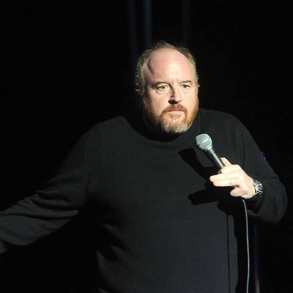 C.K. står på scen och håller i mikrofon.