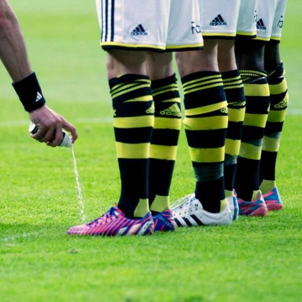 En domare sprutar en linje på gräset framför tre spelare.