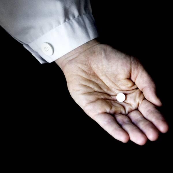 Läkare håller piller i sin hand