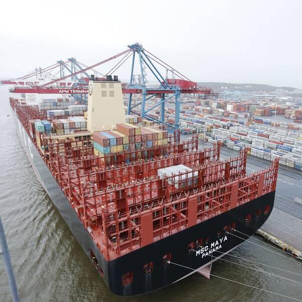 en person i en möteslokal intill en bild av ett stort containerfartyg