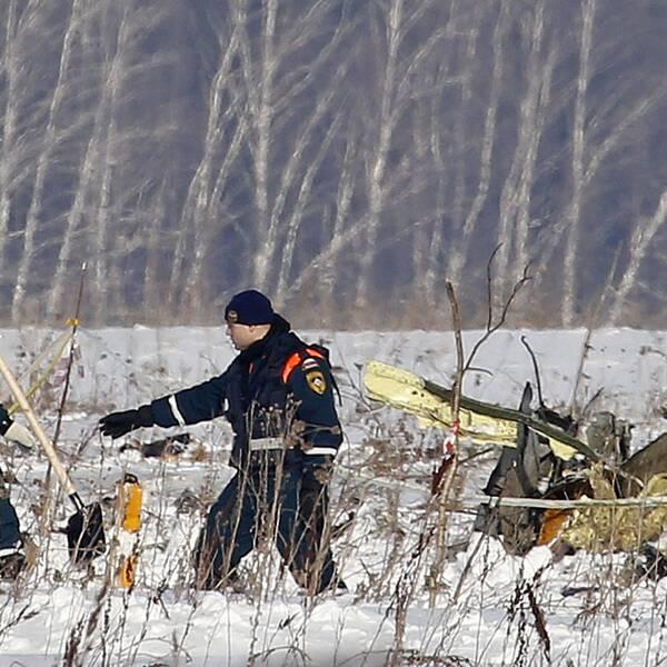 Räddningsarbetare arbetar vid platsen där det ryska flygplanet kraschade på söndagen.