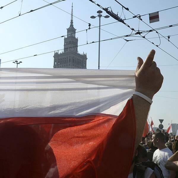 En man håller upp en polsk flagga i Warsawa.