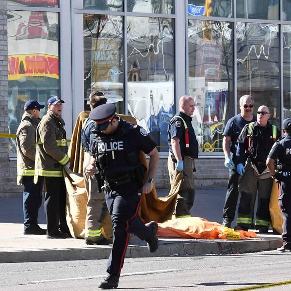 Polis och brandmän står intill döda människor som är övertäckta med filtar.