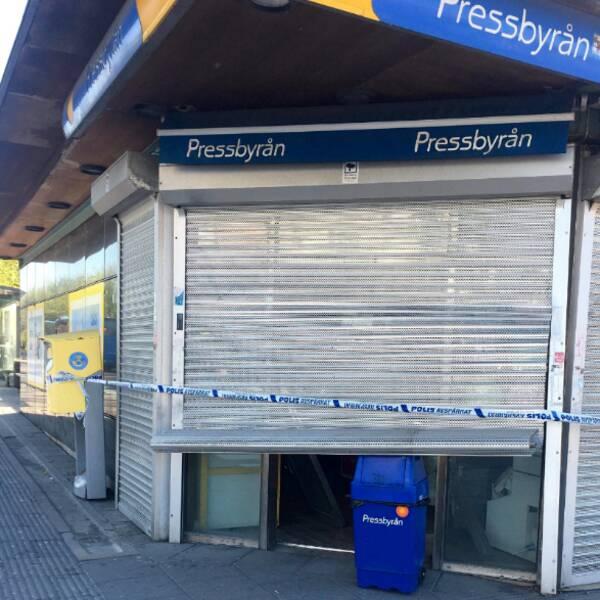 Dubbelbild. Polisbil och folksamling framför butiken. Närbild på butiken där jalusin är till hälften neddragen mot en papperskorg och polisband framför.