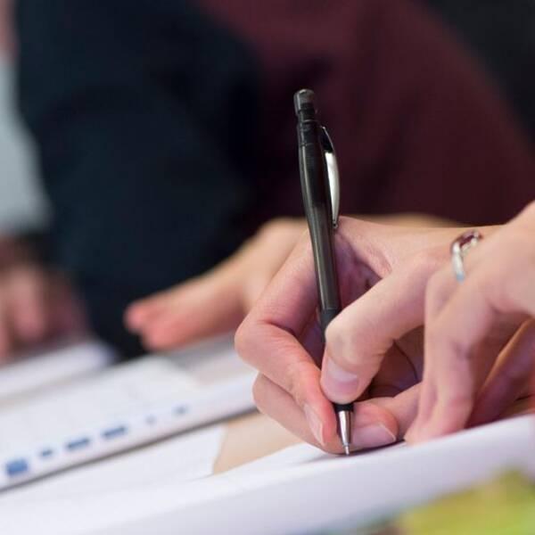 En elev sitter och skriver i en mattebok.