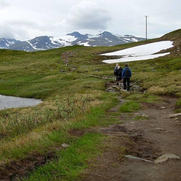 två personer vandrar på en led i fjällmiljö, förbi en sjö, en snöfläck. berg i bakgrunden