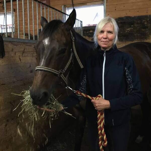 Ridhuschef Lotta Andersson med häst som äter hö