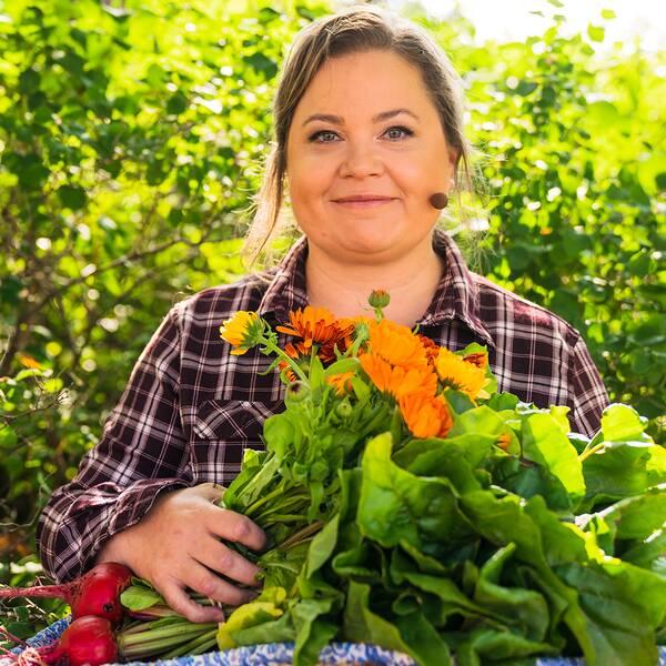 Susanne Jonsson står framför ett grönt buskage med ett stort fång grönsaker och blast i famnen. Hon småler rakt in i kameran.