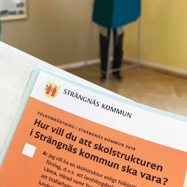 Valsedel och valkuvert, i bakgrunden syns två röstskynken i vallokalen i Härad i Strängnäs