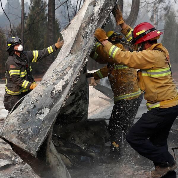 Räddningsarbetare hjälps åt att leta efter kvarlevor i ruinerna av ett hus.