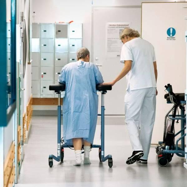 En kvinnlig patient med en rollator får hjälp av personal att ta sig fram i en korridor på ett sjukhus