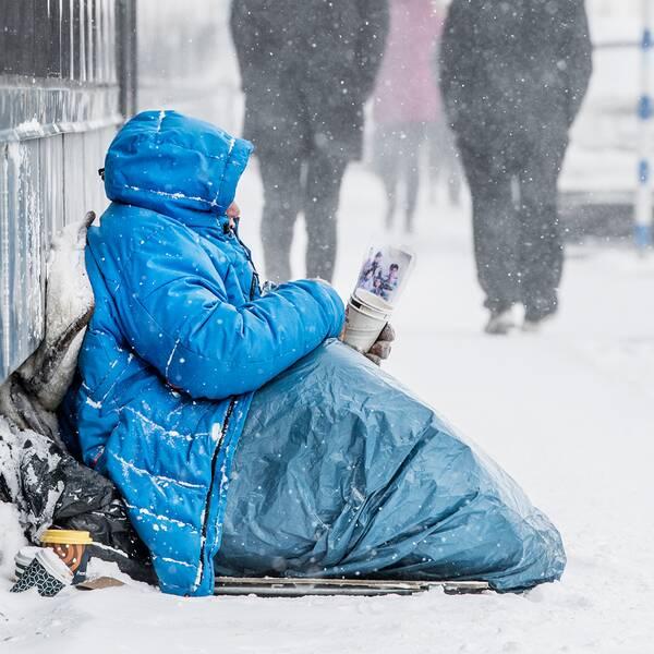 En person med tjock jacka sitter med en pappersmugg på marken