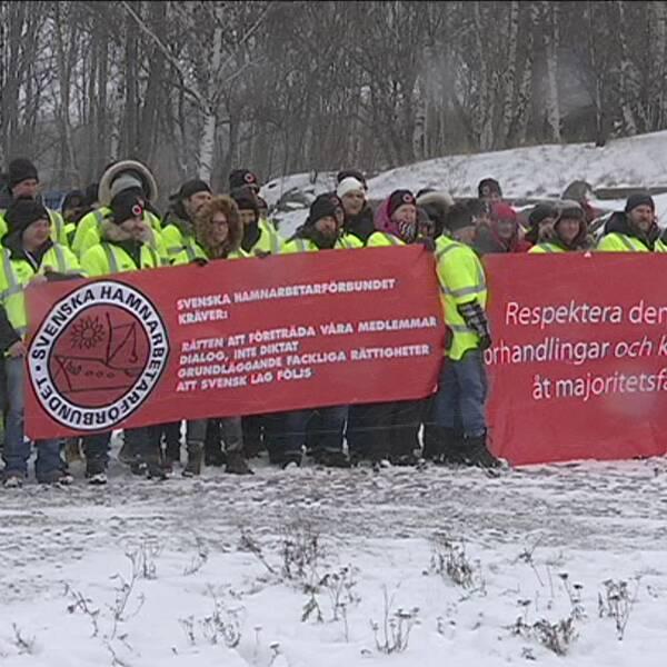 Bild av strejkande hamnarbetare med banderoll.
