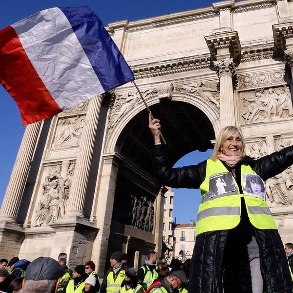 En demonstrant i gul väst viftar med den franska flaggan framför Triumfbågen i Marseille