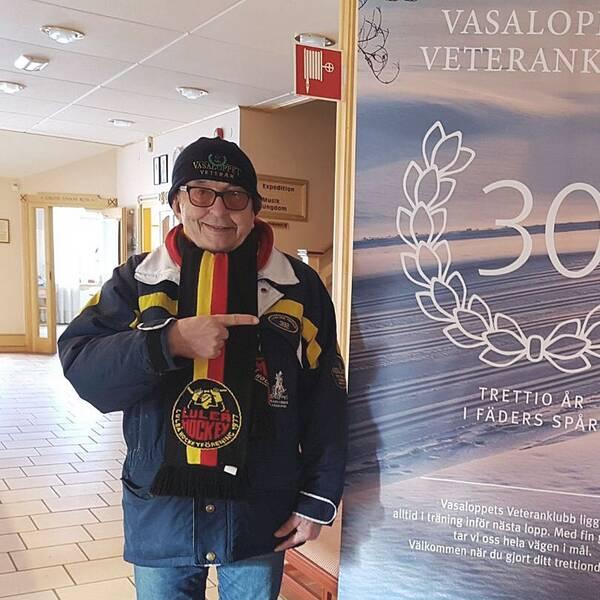 En äldre man ler och pekar på en skylt där det står Vasaloppets Veteranklubb.
