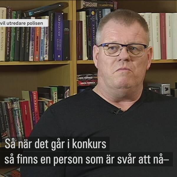 Ulf Sparring, polisens civila utredare, sitter i svart v-ringad tröja. i bakgrunden står en bokhylla full med böcker.