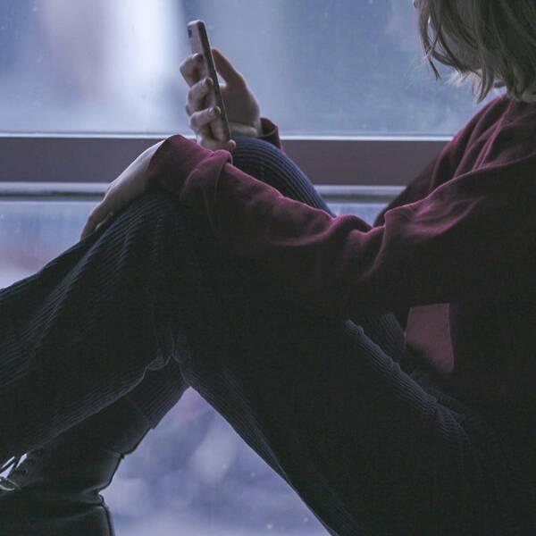 Ung person sitter vid ett fönster och tittar på mobilen.