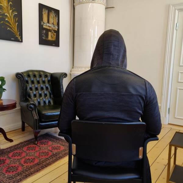 Man sitter på en stol med ryggen mot kameran